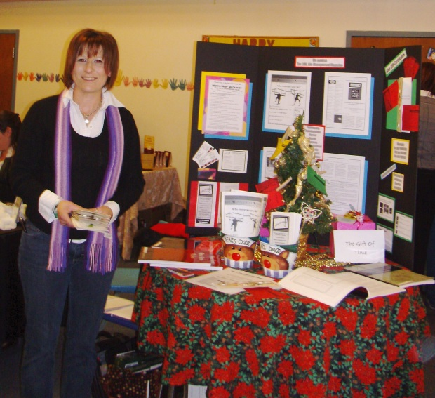 Image of Christine with a display of her faith-based workbooks and workshops